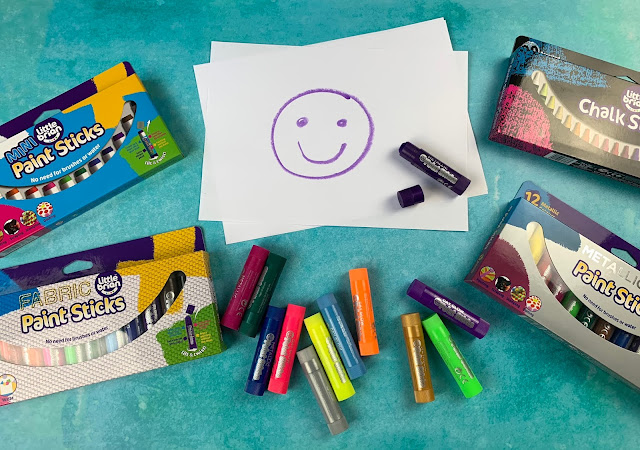 A smily face on paper surrounded by packets of Little Brian paint and chalk sticks