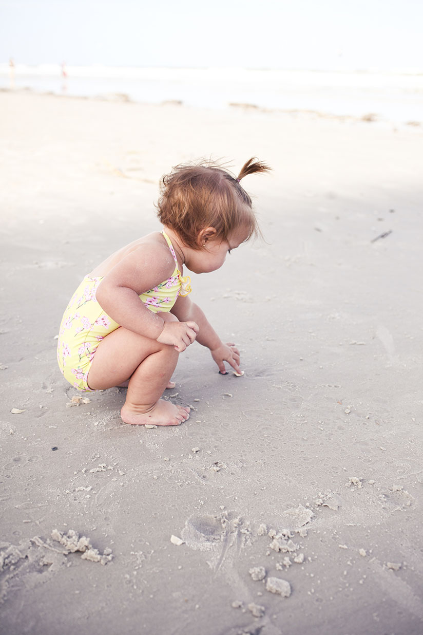 Toddler playing in the sand wearing swimwear by Sunuva
