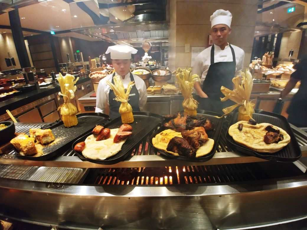 Chefs grilling steak at the grill station of The Grand Kitchen