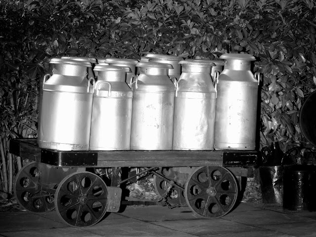 Night photo of milk churns on a railway station barrow at the Severn Valley Railway, Kidderminster