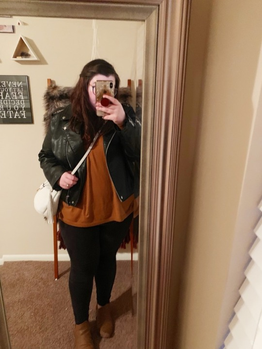 A mirror selfie of an outfit of black faux leather moto jacket, light tan-brown sweater, black faux suede moto leggings, and brown booties.