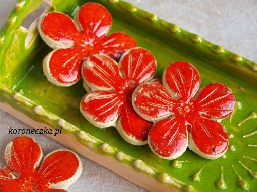 Dwie miseczki ceramiczne na ciastka i kwiatki ceramiczne czerwone.