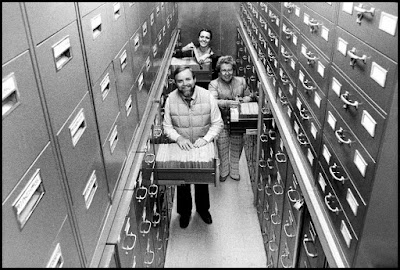 Some guys at the Smithsonian Institute poke around in file cabinets.