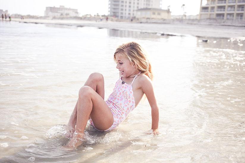 Little girl plays in the surf in Jacksonville Beach wearing Sunuva swimwear