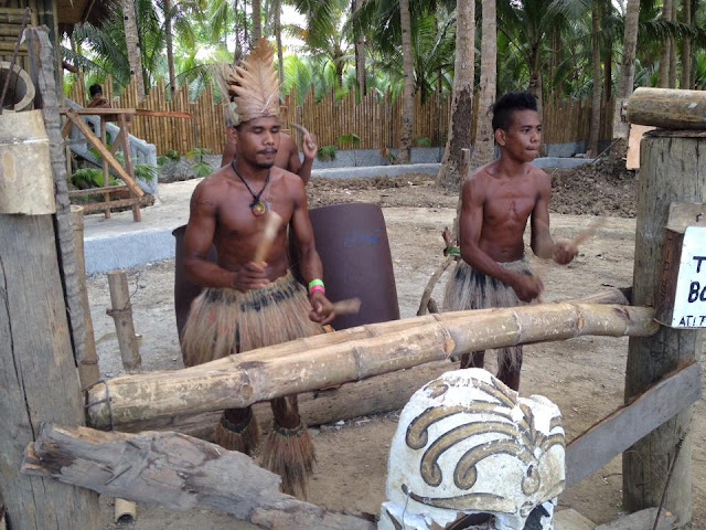 Men of the Ati tribe beating drums