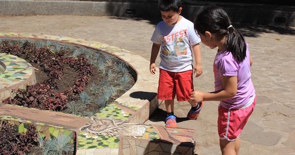 niño y niña miran mosaico de pileta en Salamanca