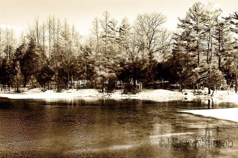 A light covering of snow blankets the areas surround an open portion of a small lake.