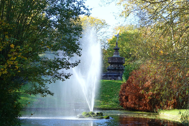 autumnal shot of the lake, statue, trees and water feature in sefton park, liverpool