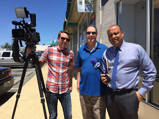 WJLA reporter Horace Holmes (right), with his cameraman (left) and Mark Wright, working on storefront crash story.