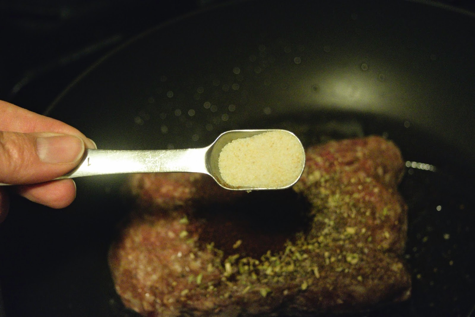 Onion powder being added to the ground beef in the pan.