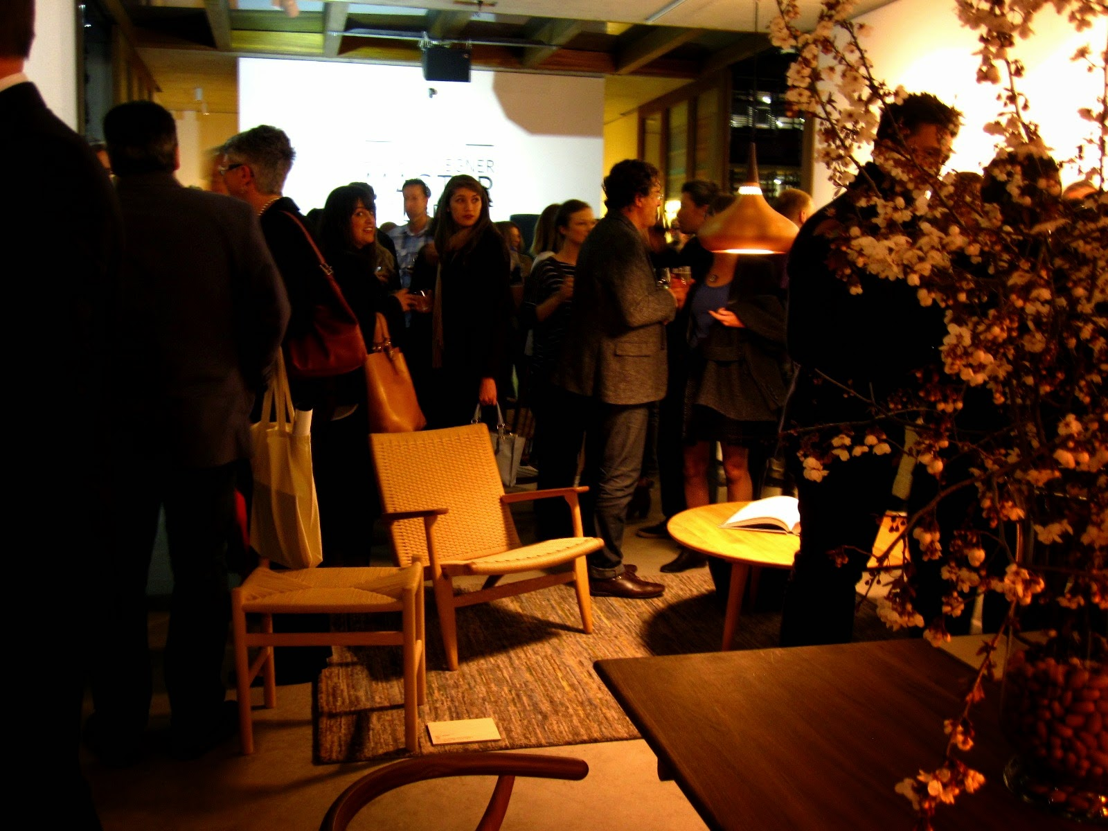 Crowd at a gallery opening. A Hans Wegner table and chair are in the foreground and a stool, armchair and coffee table in the background.