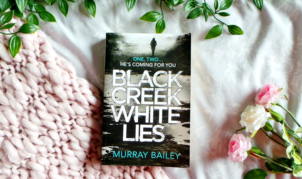 Black Creek White Lies Book resting on a pink chunky knit blanket next to 3 roses