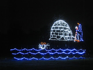 Light display: Diving penguin splashes into the water near an igloo, Vasona Lake County Park, Los Gatos, California