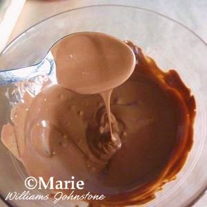 Melted chocolate in a glass bowl dripping off a spoon