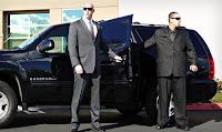 Siyah bir cipin kapısını açan uzun boylu, takım elbiseli ve gözlüklü korumalar etrafa bakarken
