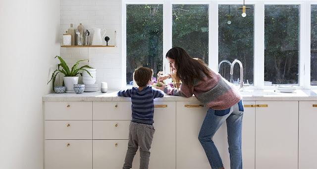Eine Frau steht mit einem Kind in einer Küche