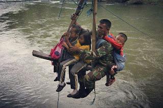 Meluncur Pakai Tali dan Gendong Bocah, Prajurit TNI Ini Bantu Anak-anak Sekolah Menyeberangi Sungai