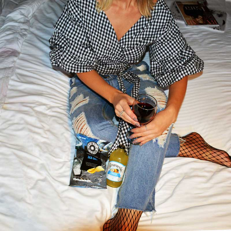 from above instagram shot of girl wearing gingham wrap blouse on hotel bed with glass of red wine fishnet tights under ripped jeans