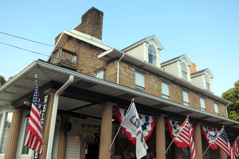 Old Stone House restaurant building with flags.