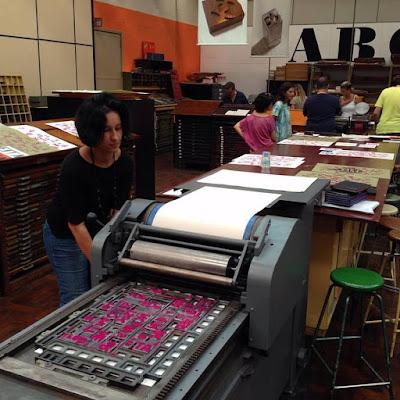 Foto da sala de aula com os alunos realizando alguns testes. Com destaque para uma moça iniciando o processo de impressão