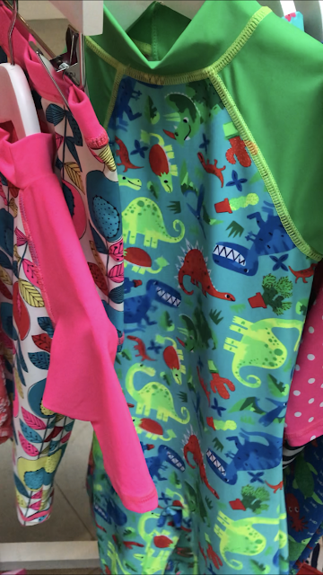 a close up a green and blue swimsuit with long sleeves, high neck and dinosaur print