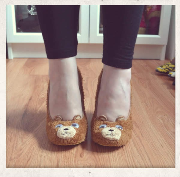 feet facing forward wearing brown fur bear shoes with face