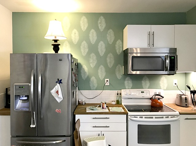apartment kitchen with leaf designed wall