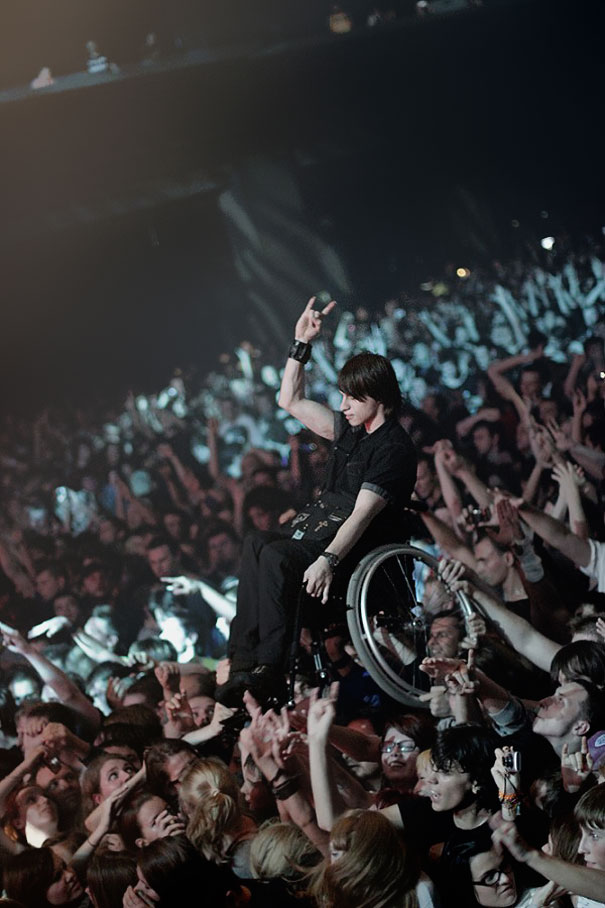 Fans hold up handicapped friend at korn concert in moscow.