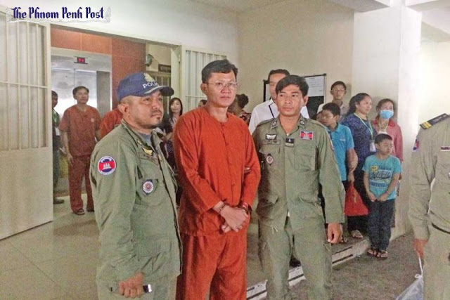 Election official and former Adhoc staffer Ny Chakrya is escorted out of the Phnom Penh Municipal Court yesterday after his hearing. Niem Chheng