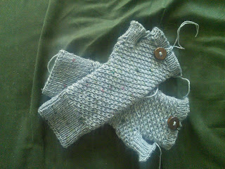 A pair of blue-grey mittens with dark wood buttons at the top cuff.  There are wool ends hanging off both mittens.