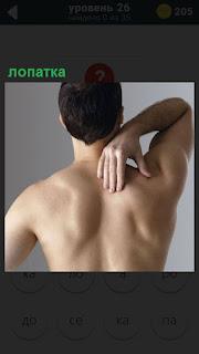 Мужчина рукой за спину берется за лопатку свою, стоит спиной