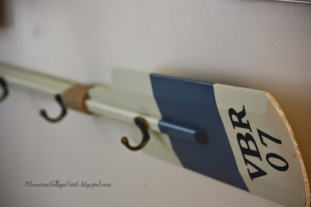 photo of a rowing oar with hooks to hang things on on the wall | sea side living room | rosevinecottagegirls.com