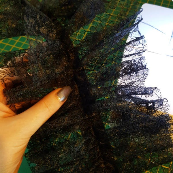 holding the gathered, sewn lace material in hand