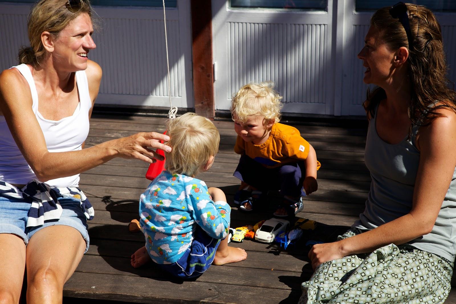 Lotta Löfwall sitter och pratar med Alice på Sandhamn medan barnen leker
