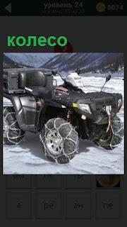В зимних условиях между гор двигается машина, на колеса которой одеты цепи для лучшей проходимости