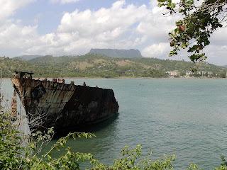 Baracoa, Kuba, Blick über Hafeneinfahrt, im Vordergrund rostiges Wrack, im Hintergrund El Yunque.