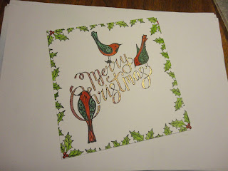 Christmas image with red and green birds, holly border, shimmery writing