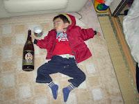 Lustiges asiatisches Kleinkind schläft neben Alkoholflasche