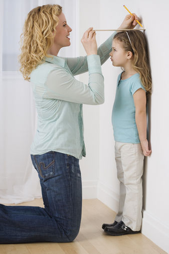 A mother measuring her child's height
