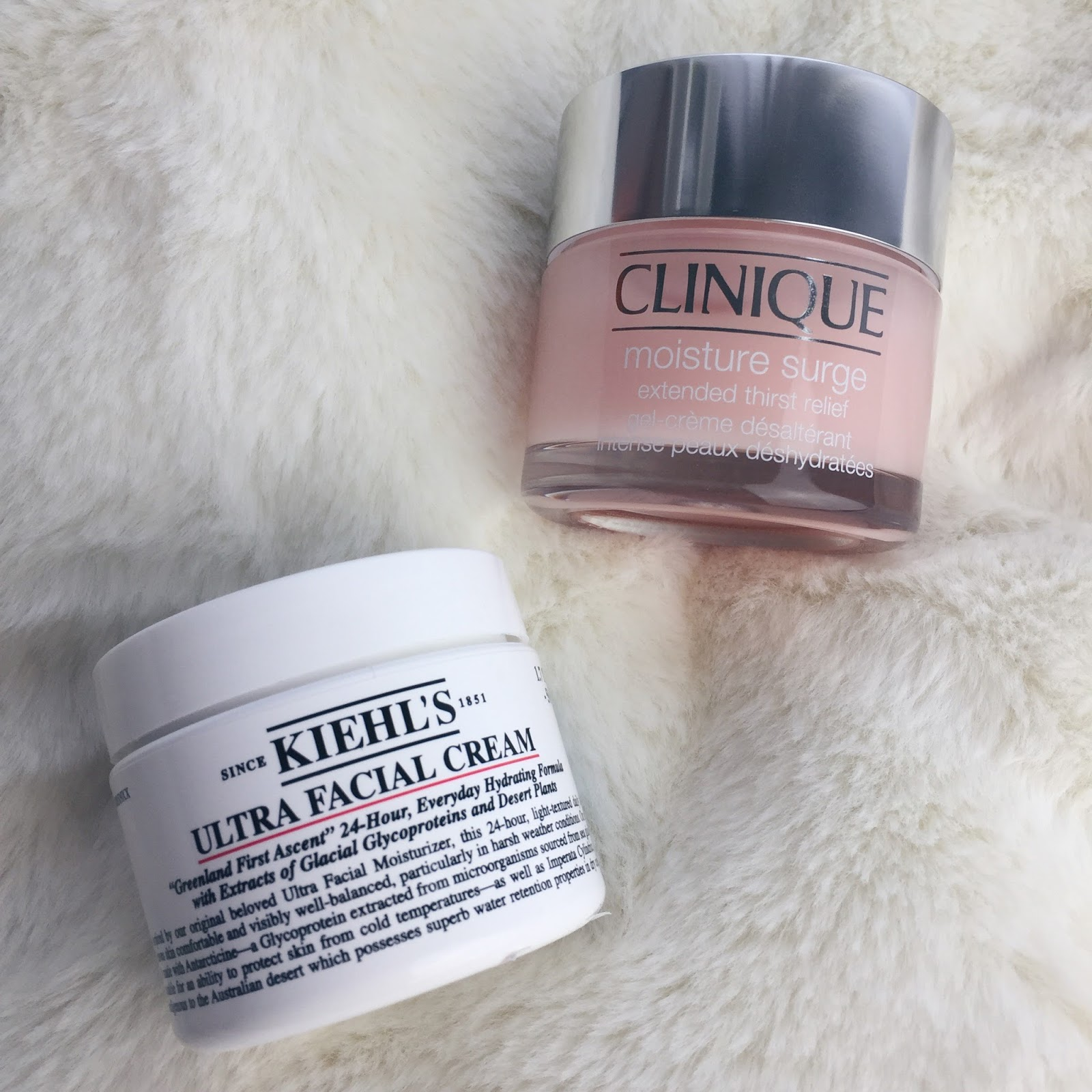 Kiehl's ultra facial cream a Clinique moisture surge extended thirst relief vedle sebe na hebké podložce