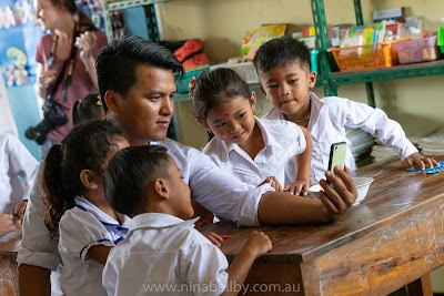 Teacher surrounded by four kindergarten children looking at his phone whilst they take a selfie