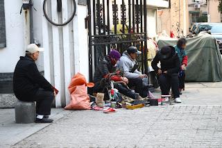 Utcai cipészek dolgoznak Shanghai egyik utcáján.