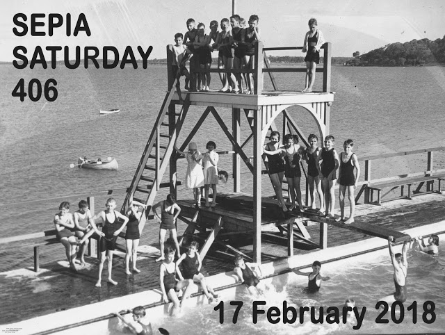 This image depicts a swimming class for local school children. They are gathered on the diving tower and diving board. The water of the bay at Manly can be seen in the background.