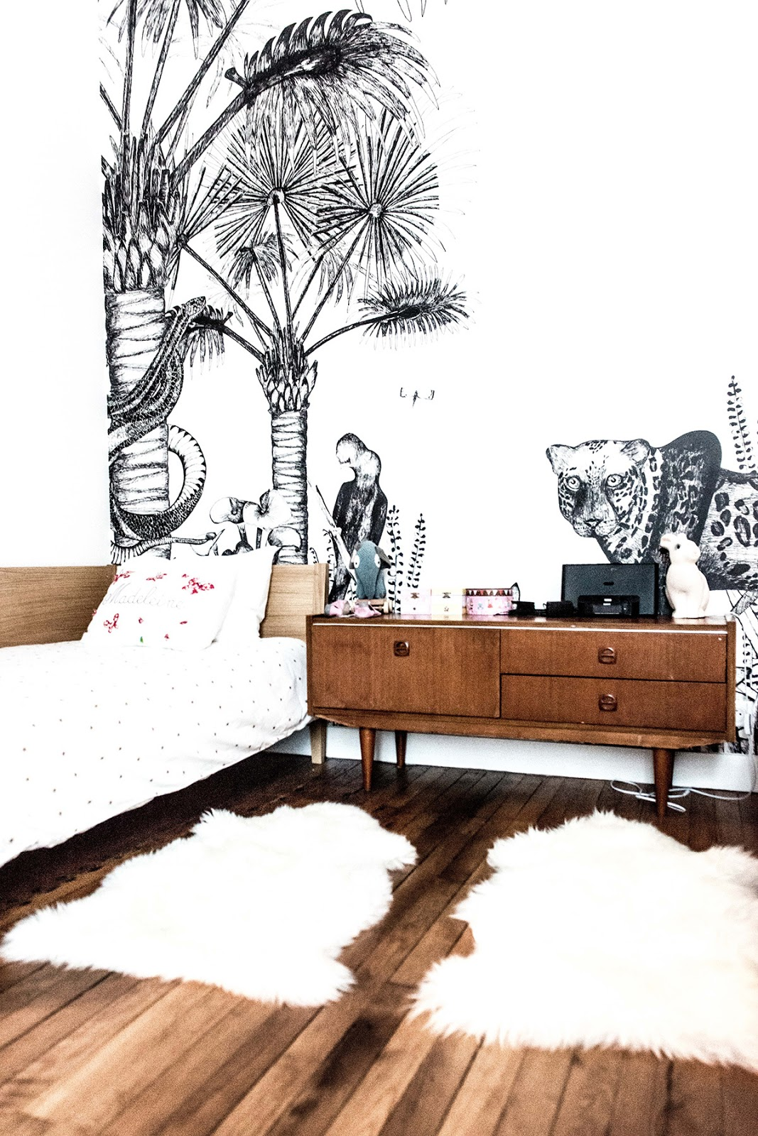 Bedroom with a wallpaper and mid century modern sideboard inside of stylish paris apartment