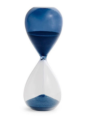 hourglass, half blue and half clear, with blue sand