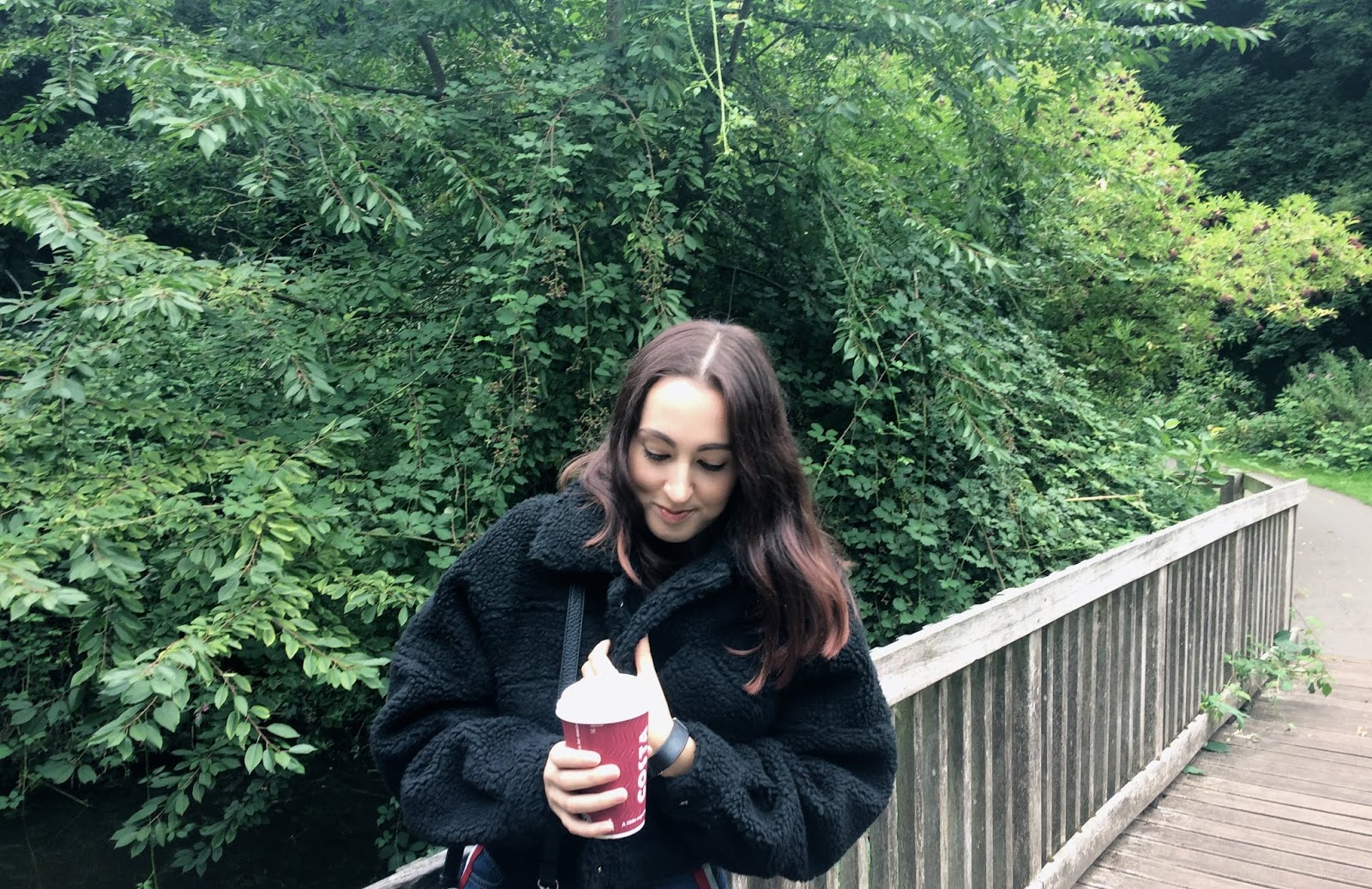 Outdoors on a bridge wearing a cosy cropped black jacket