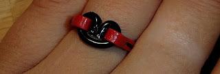 Vue sur une main de la bague rouge avec motif coeur