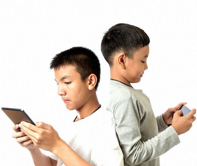 De costas um para o outro, absorvidos pelo dispositivo móvel.