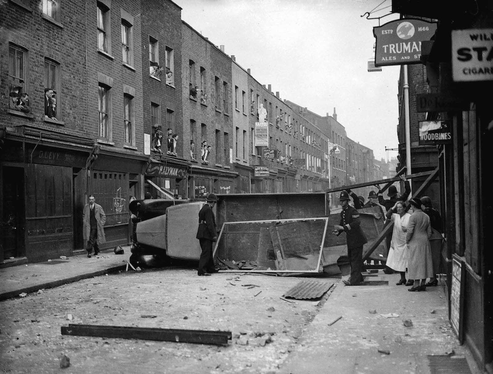 East London - Police remove an overturned lorry used as a barricade during the Communist-Fascist riots in Cable Street. 1936.