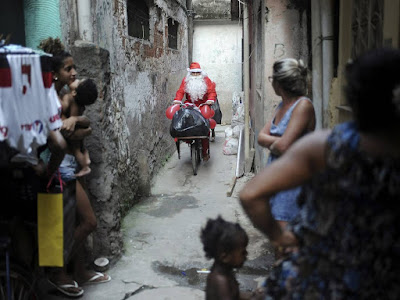 Santa Claus riding on a bicycle in a small gray alley. There are people in the foreground watching his approach.